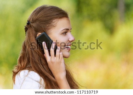 Young smiling pretty woman talking on mobile phone profile, against background of autumn park. - stock photo