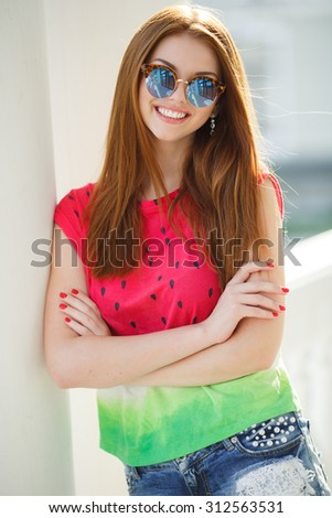 Young smiling redhair woman with sunglasses outdoors. Soft sunny colors.Close portrait  - stock photo