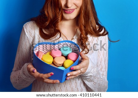 Young smiling redhead woman hold box with multicolored french macaroon . Trendy sweet  colorful confections in heart box - stock photo