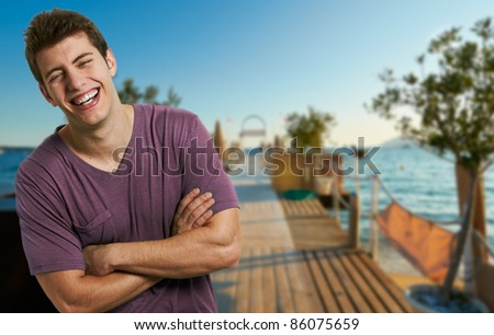 Young smiling relaxed man at the beach in a summer day - stock photo