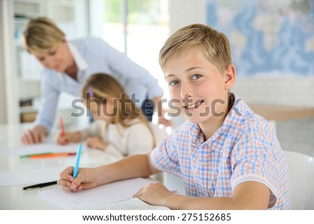 Young smiling schoolboy in classroom - stock photo