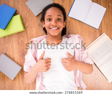 Young smiling schoolgirl laying on the floor with some  and making thumbs up. - stock photo