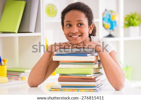 Young smiling schoolgirl sitting at the table with stack of books on colorful background. - stock photo