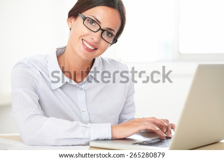 Young smiling secretary with spectacles using her laptop while looking at you - stock photo