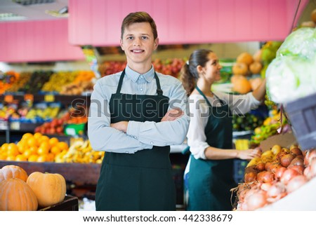Young smiling sellers having vegetables and fruits on displays of market