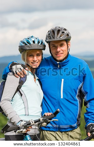 Young smiling sporty couple with bicycles in helmet - stock photo