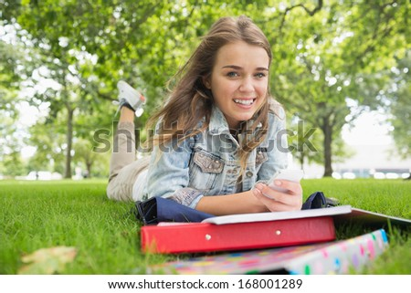 Young smiling student lying on the grass sending a text on college campus - stock photo