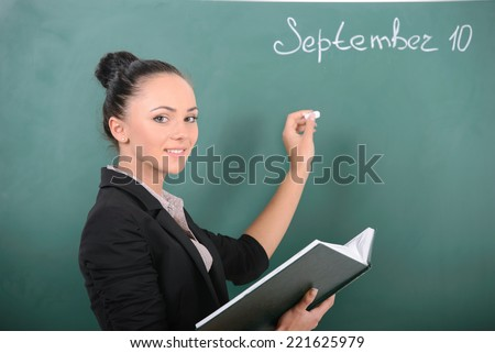 Young smiling student or teacher at the blackboard - stock photo