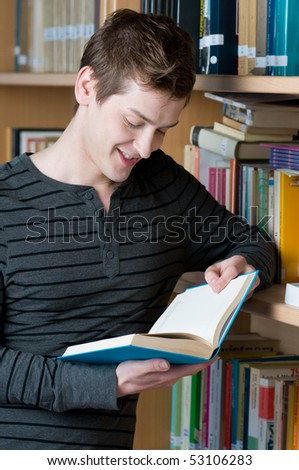 Young smiling student reading a book in a library - stock photo