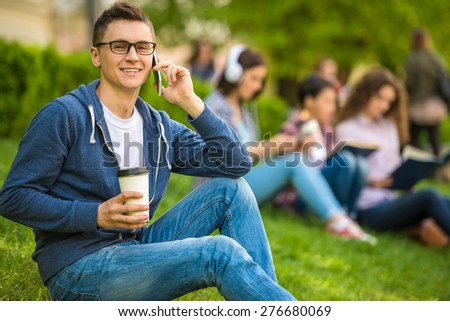 Young smiling student sitting on the lawn with cup of coffee and reading book. - stock photo