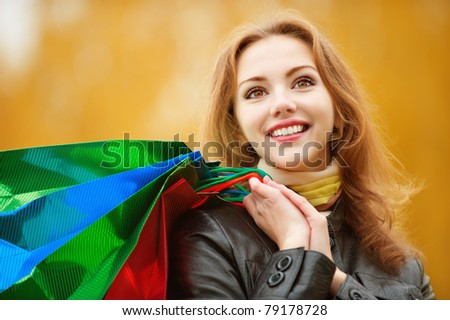 Young smiling student with purchases in packages comes back from shop against yellow autumn nature. - stock photo