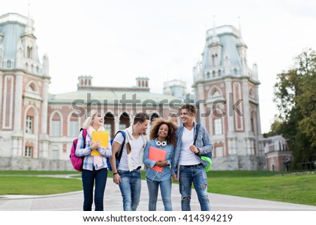 Young smiling students on campus - stock photo
