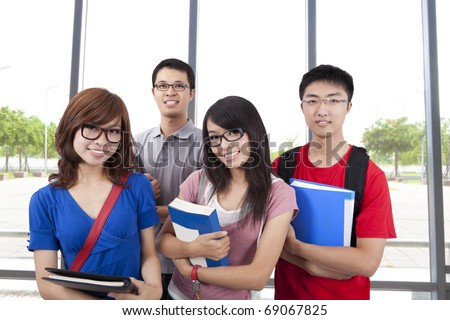 Young smiling students stand in the classroom - stock photo