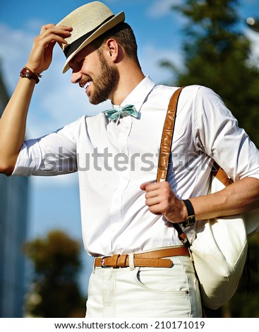 Young smiling stylish sexy handsome model man tourist in casual cloth lifestyle in the street in hat with bag - stock photo