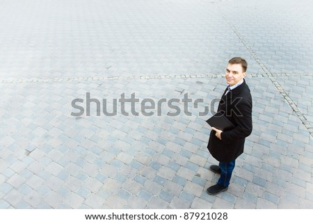 Young smiling successful businessman holding laptop. Large copy space for any text