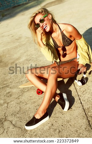 Young smiling tanned sexy hot laughing girl in bikini sitting alone in summer and have fun  - stock photo