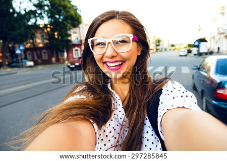 Young smiling teen happy woman making selfie on the street, ling hairs, bright make up and cute clear glasses, traveling alone, having fun, positive mood, joy, vacation. - stock photo