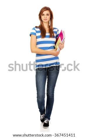 Young smiling teenage woman holding books