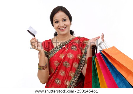 Young smiling traditional woman with shopping bags and credit card