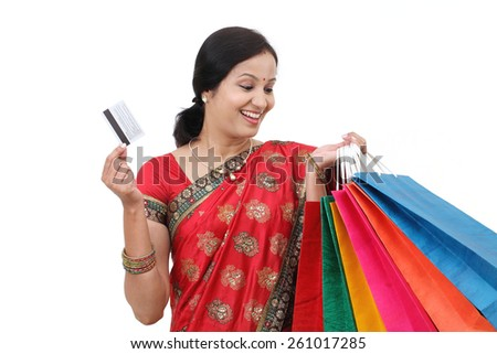 Young smiling traditional woman with shopping bags and credit card - stock photo