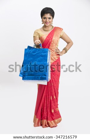 Young smiling traditional woman with shopping bags on white background. - stock photo