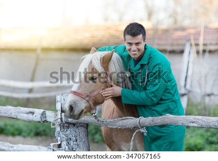 Young smiling veterinarian cuddling horse on the ranch - stock photo
