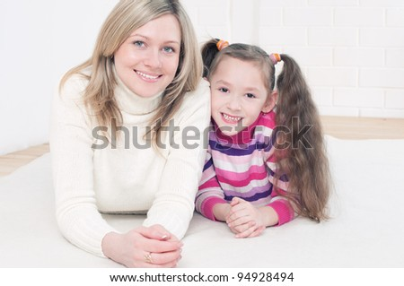Young smiling woman and her cute little daughter lying on the floor