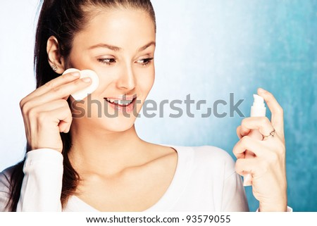 young smiling woman apply foundation with sponge applicator, studio shot