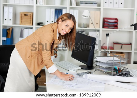 Young smiling woman architect at her work table - stock photo