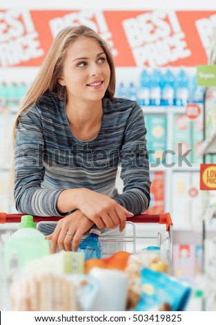Young smiling woman at the supermarket, she is shopping and pushing a cart along the store aisles