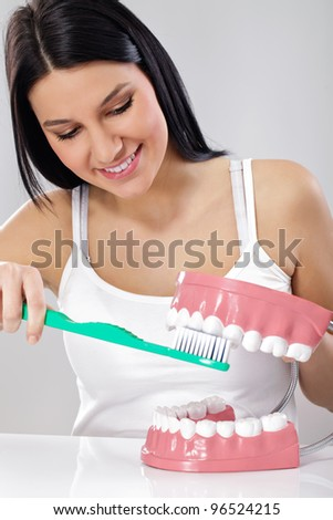 Young smiling woman brushing teeth on plastic model jaws - stock photo