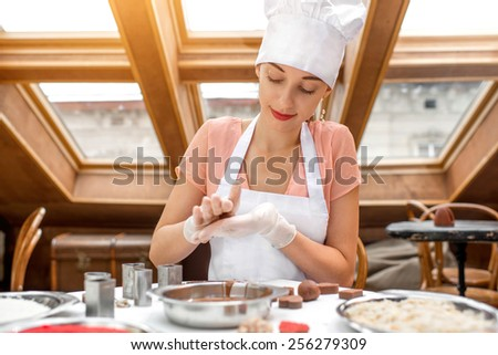 Young smiling woman chef dressed in white pinafore making handmade chocolate candy in the cafe