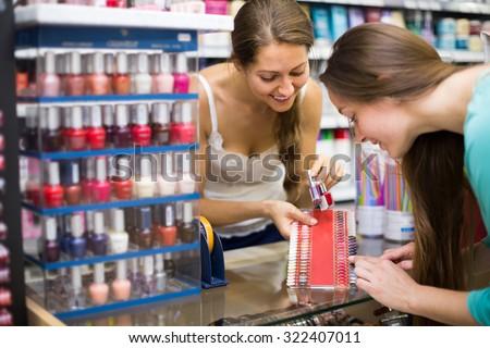 Young smiling woman choosing new nail polish tone at cosmetic shop  - stock photo