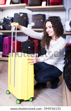 Young smiling woman choosing travel suitcase in haberdashery store