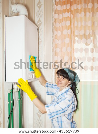 young smiling woman cleaning a boiler with a rag