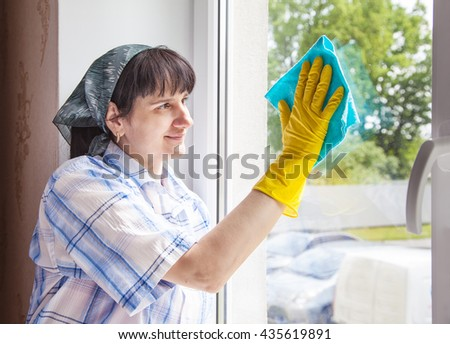 young smiling woman cleaning a window with a rag closeup