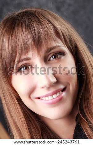 Young smiling woman close up portrait. Beauty caucasian girl looking straight into camera.