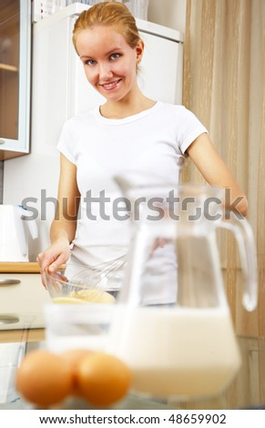 young smiling woman cooking in the kitchen - stock photo