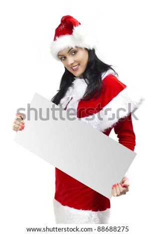 Young smiling woman dressed in Santa Claus holding a blank board - stock photo
