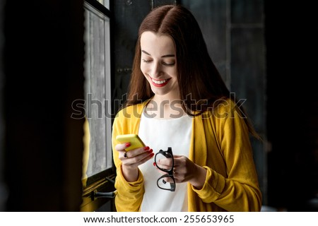 Young smiling woman dressed in yellow using phone near the window in the dark interior - stock photo