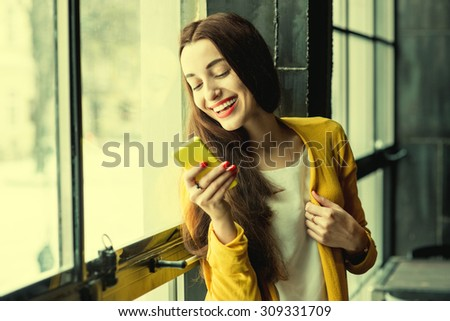 Young smiling woman dressed in yellow using phone near the window in the dark interior. Photo with cross processing filter - stock photo