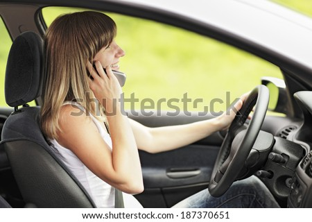Young smiling woman driving a car. Looking at rear-view mirror