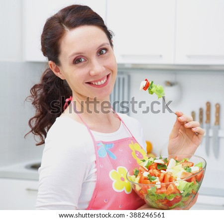 young smiling woman eating vegetables salad at kitchen