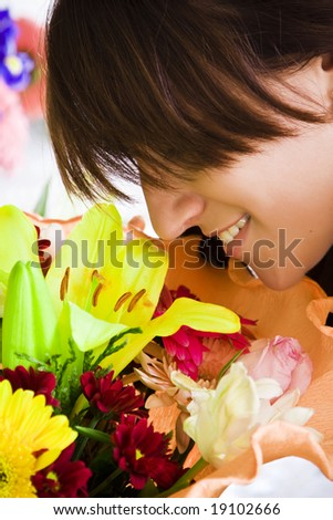 Young smiling woman enjoying a bouquet fragrance. - stock photo