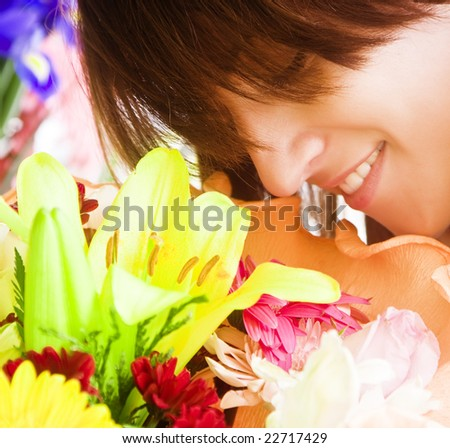 Young smiling woman enjoying a bouquet fragrance. Squared composition. - stock photo