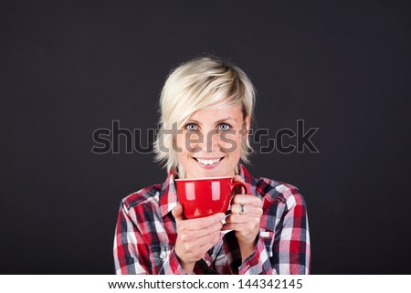 Young smiling woman enjoying coffee against black background - stock photo