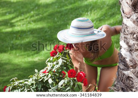 Young smiling woman enjoying her time at vacation, smelling flowers. Vacations And Tourism Concept.