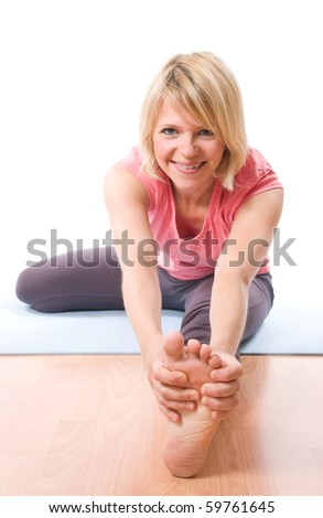 Young smiling woman exercising holding her foot