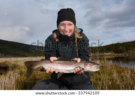 Young smiling woman fishing a big arctic trout, Patagonia, Chile - stock photo