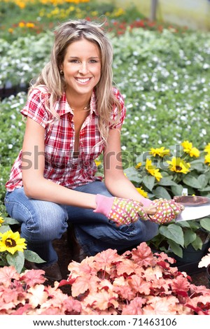 Young smiling woman florist working in the garden - stock photo